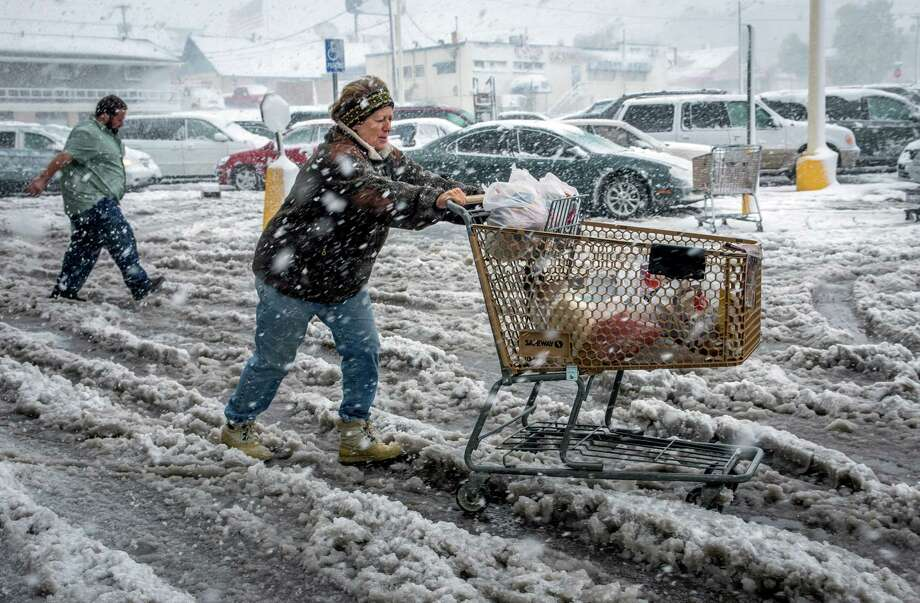 Brenda Nolting, of Rapid City, S.D., rolls her cart to her car after stocking up on necessities Friday, Oct. 4, 2013 at a local supermarket in Rapid City. An early snow storm has swept through Wyoming and western South Dakota, dropping more than a foot of snow in places. Photo: AP