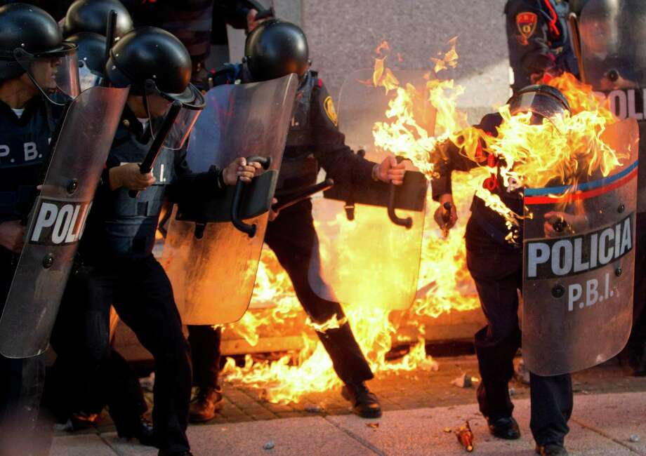 A police officer is engulfed in flames after being hit by a Molotov cocktail thrown by protesters on the anniversary of the Tlatelolco massacre in Mexico City, Wednesday Oct. 2, 2013. Mexico commemorated the 45th anniversary of the massacre of students holding an anti-government protest, killed by men with guns and soldiers 10 days before the 1968 Summer Olympics celebrations in Mexico City. Photo: AP