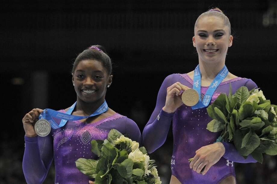 Simone Biles, left, and McKayla Maroney show their medals on the podium after taking the double on the vault exercise during the apparatus final on Saturday. Photo: Yves Logghe, Associated Press