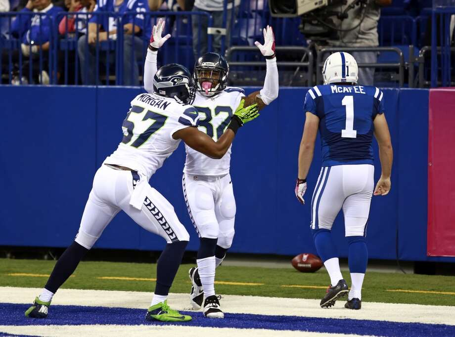 Seattle Seahawks outside linebacker Mike Morgan, left, and strong safety Jeron Johnson celebrates a safety in front of Indianapolis Colts punter Pat McAfee during the first half of an NFL football game in Indianapolis, Sunday, Oct. 6, 2013. (AP Photo/Brent R. Smith) Photo: Brent R. Smith, AP