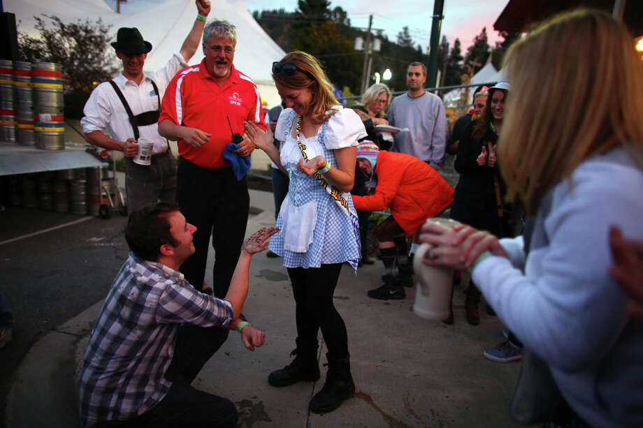 Eric Mathiasen gives a muck-covered engagement ring back to his fiance, Kathy Henriksen after it was recovered from a storm drain during the first weekend of the annual Leavenworth Oktoberfest. A crowd gathered as men dangled their bodies into the opened drain to try and recover the ring. Photo: JOSHUA TRUJILLO, SEATTLEPI.COM / SEATTLEPI.COM