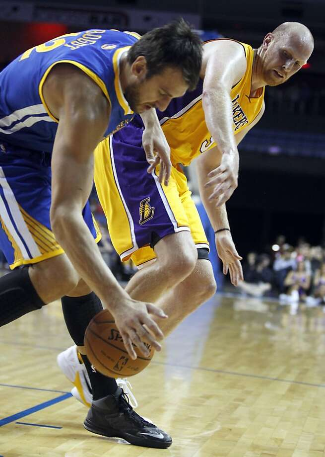 Andrew Bogut (left) steals the ball from the Lakers' Chris Kaman in the Warriors' 104-95 exhibition loss Saturday. Photo: Alex Gallardo, Associated Press