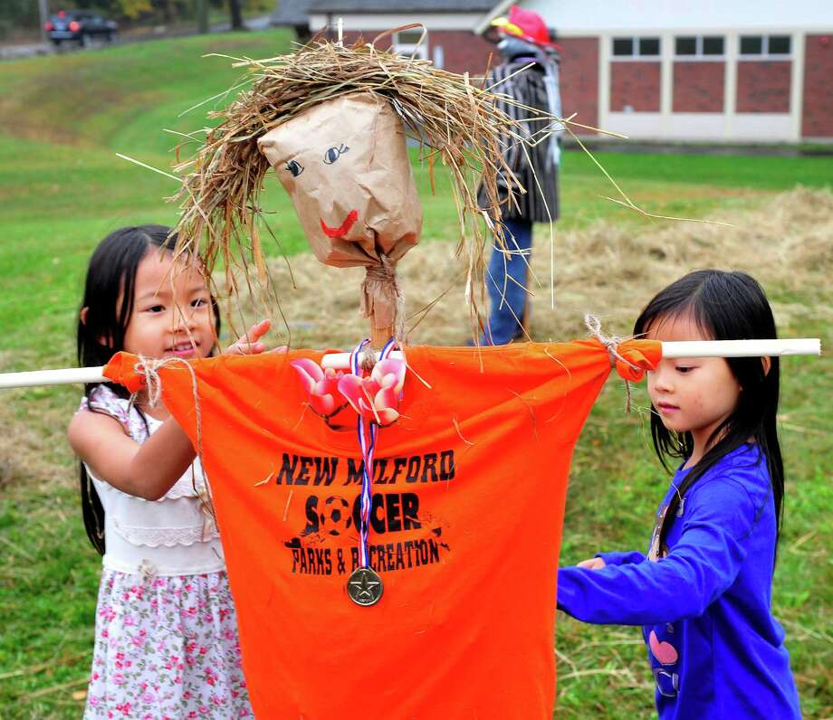 Sarah Seo, 8, left, and her sister, Hannah, 6, work on a scarecrow, during Brookfield Day in Brookfield, Conn. Sunday, Oct. 6, 2013. Photo: Michael Duffy / The News-Times