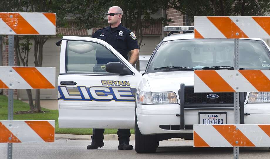 A Bryan police officer blocks off an apartment complex that was raided by the FBI this morning. The raids were connected to FBI operations in two upscale Houston neighborhoods. (The Eagle / Bryan-College Station)