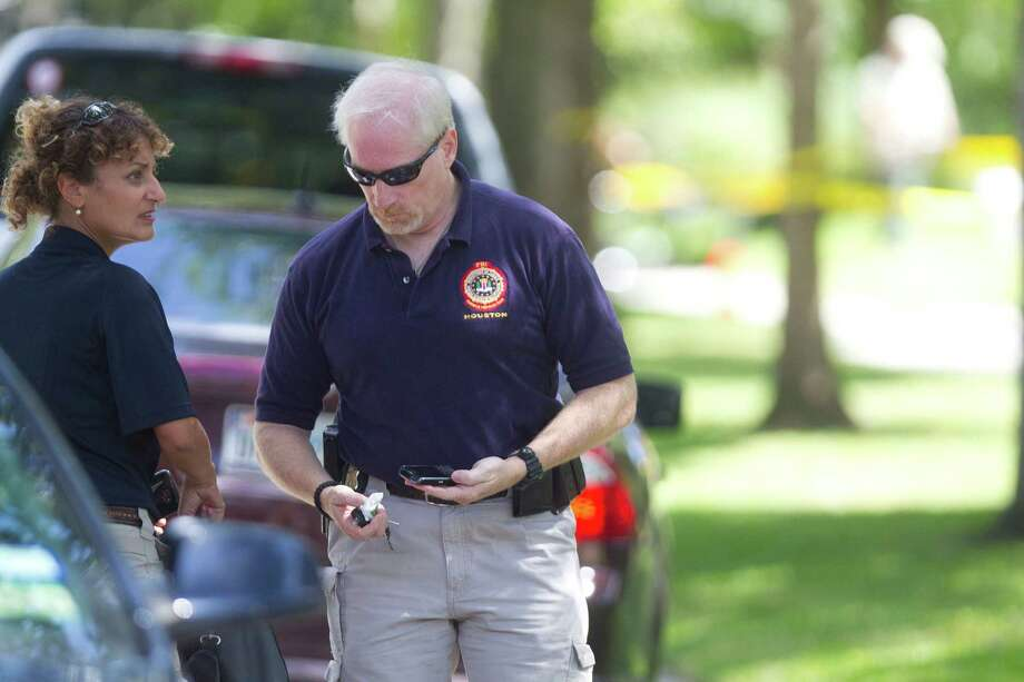A member of the FBI Evidence Response Team arrives at the scene where FBI agents conducted a search a upscale home on the 2000 block of Albans near Rice Village in the Southampton neighborhood Friday, Oct. 4, 2013, in Houston. Another site was being searched simultaneously at 411 Fall River Road in the Memorial area. Federal officials said they could not release other information because documents in the case have been sealed. Agents entering the home on Albans are wearing protective clothing, including purple gloves, white long-sleeve suits, and high, yellow boots. Two agents were also being suited up with masks rigged with a breathing apparatus. Photo: Johnny Hanson, Houston Chronicle / Houston Chronicle
