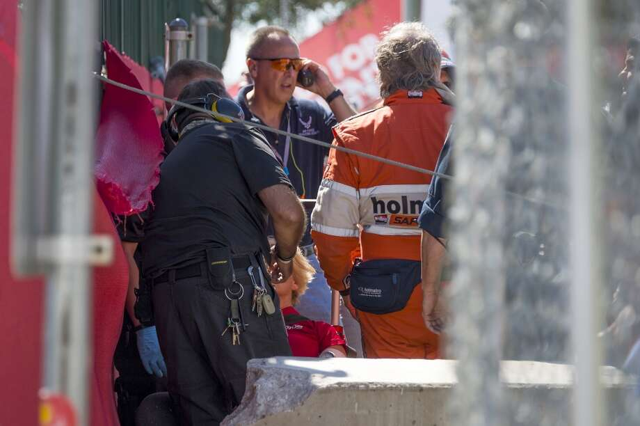 Emergency personnel and track workers respond to the scene of a crash by Dario Franchitti during the second IndyCar Grand Prix of Houston auto race on Sunday. Photo: Smiley N. Pool, Houston Chronicle