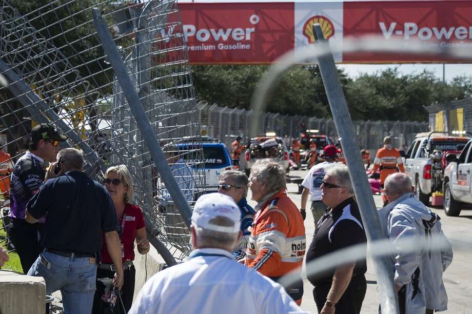 Emergency personnel and track workers respond to the scene of a crash by Dario Franchitti. Photo: Smiley N. Pool, Houston Chronicle