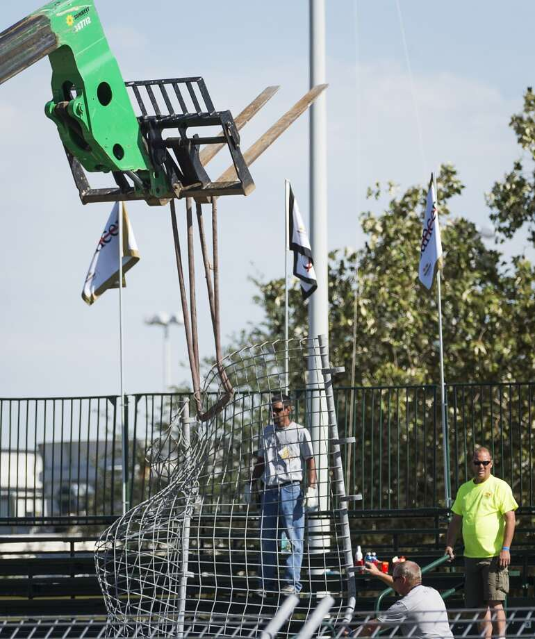 Track workers remove twisted fencing from the scene of a crash by Dario Franchitti. Photo: Smiley N. Pool, Houston Chronicle