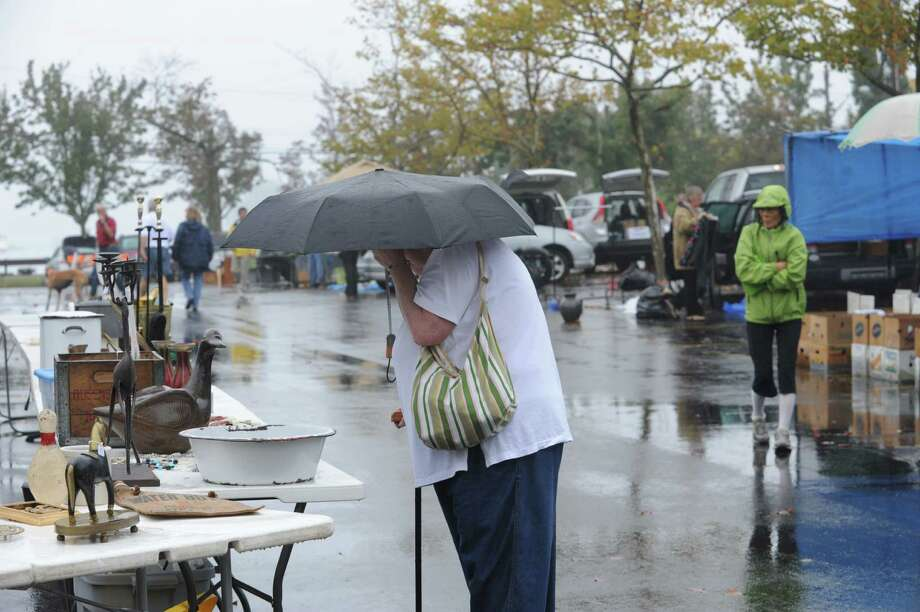 A big umbrella keeps a shopper dry at Greenwich Knights of Columbus's Annual flea market at Island Beach parking lot, in Greenwich, Conn., Sunday, Oct. 6, 2013. Photo: Helen Neafsey / Greenwich Time