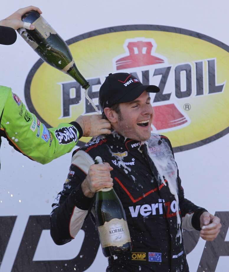 James Hinchcliffe, left, who placed third, pours champagne on first place finisher Will Power, right, after the second race. Photo: Melissa Phillip, Houston Chronicle