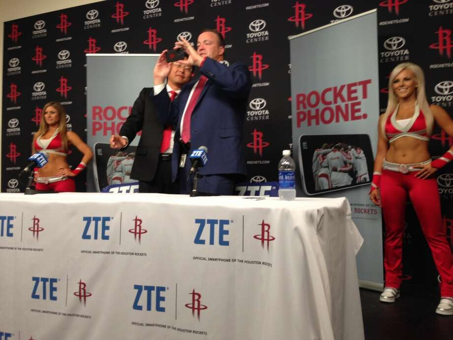 ZTE-USA CEO Lixin Cheng watches while Rockets CEO Tad Brown uses a nubia 5 smartphone to photograph reporters. Photo: Dwight Silverman, Houston Chronicle
