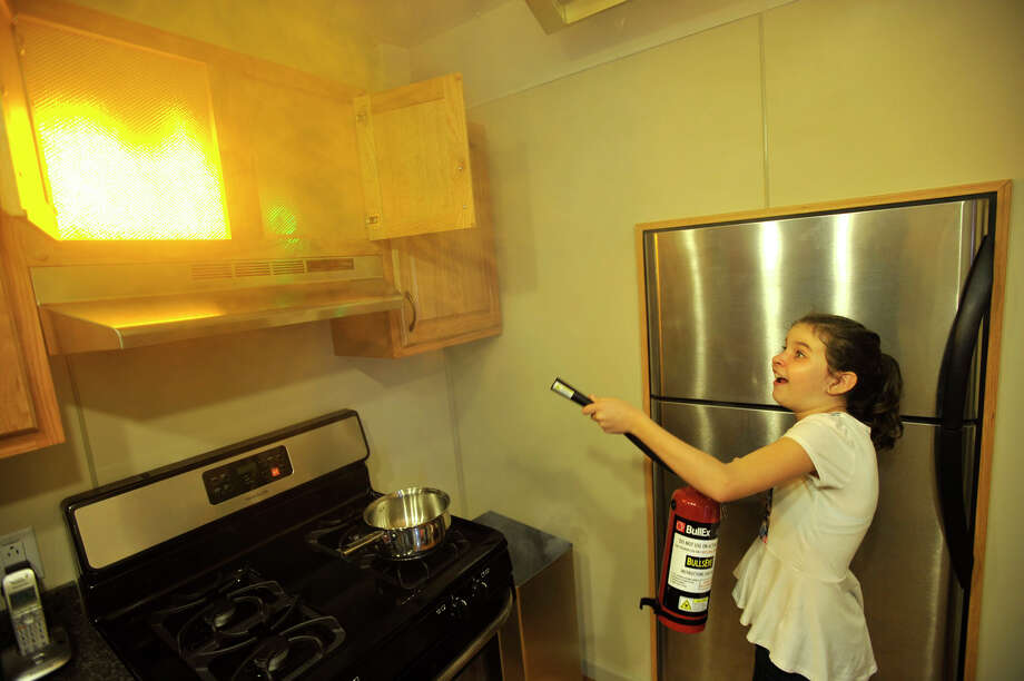 Rachel Bacon extinguishes a simulated fire in a model kitchen while learning the proper technique in stamping down many types of fires in a home setting during the open house at the Springdale fire station in Stamford, Conn., on Sunday, Oct. 6, 2013. Photo: Jason Rearick / Stamford Advocate