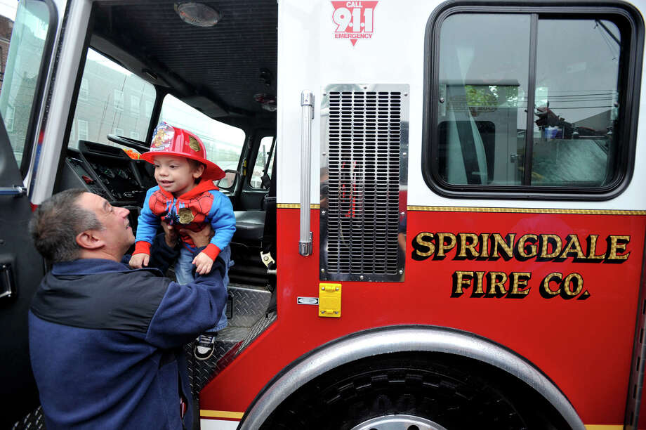 After getting a tour of the inside of a fire truck, Joshua Liscio gets help exiting the driver's seat of the truck from his grandfather, Mark Bennett, during the open house at the Springdale fire station in Stamford, Conn., on Sunday, Oct. 6, 2013. Photo: Jason Rearick / Stamford Advocate