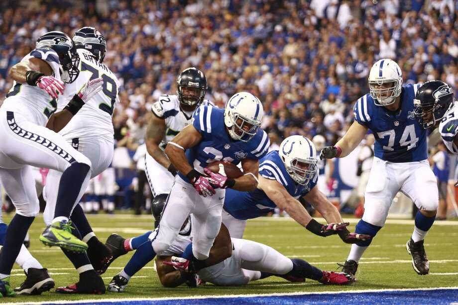 Indianapolis Colts running back Donald Brown, top, goes over Seattle Seahawks middle linebacker Bobby Wagner to score a touchdown during the second half of an NFL football game in Indianapolis, Sunday, Oct. 6, 2013. (AP Photo/Brent R. Smith) Photo: Brent R. Smith, AP