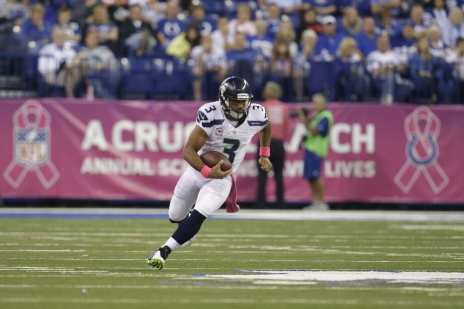 Seattle Seahawks quarterback Russell Wilson scrambles in front of a banner to promote breast cancer awareness during the first half of an NFL football game against the Indianapolis Colts in Indianapolis, Sunday, Oct. 6, 2013. (AP Photo/AJ Mast) Photo: AJ Mast, AP
