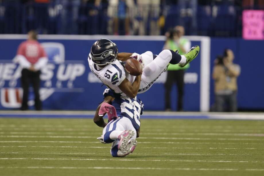 Seattle Seahawks wide receiver Golden Tate, top, looses control of the ball as he flips over Indianapolis Colts cornerback Greg Toler during the second half of an NFL football game in Indianapolis, Sunday, Oct. 6, 2013.  The pass was incomplete. The Colts defeated the Seahawks 34-28. (AP Photo/AJ Mast) Photo: AJ Mast, AP