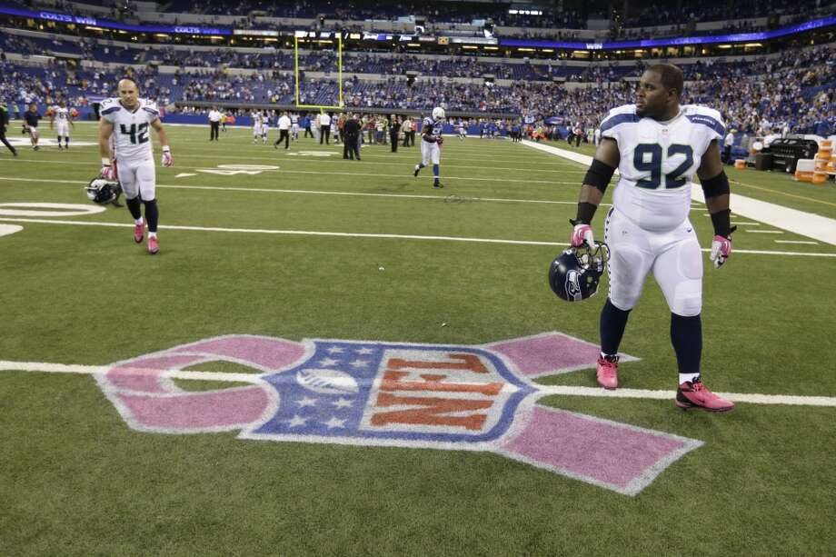 Seattle Seahawks defensive tackle Brandon Mebane walk off the field past a logo to promote breast cancer awareness following an NFL football game against the Indianapolis Colts in Indianapolis, Sunday, Oct. 6, 2013.  The Colts defeated the Seahawks 34-28. (AP Photo/Michael Conroy) Photo: Michael Conroy, AP