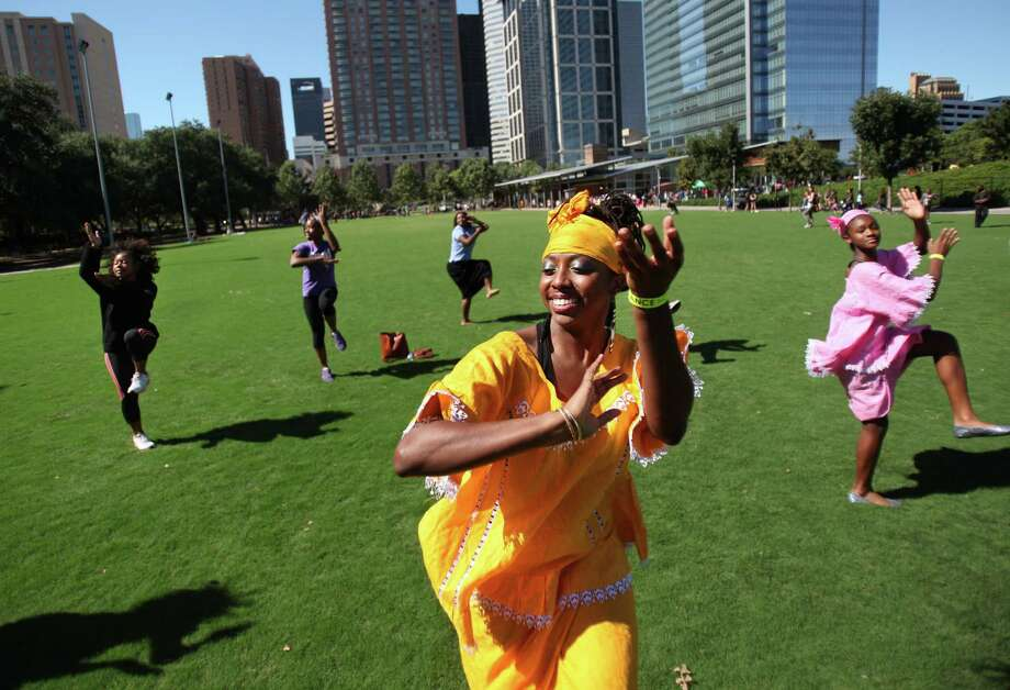 (Left to right) Alana Taylor, of Koumanke'Le' African Dance & Drum Ensemble, teach Discover Dance attendees how to dance at Discovery Green on Sunday, Oct. 6, 2013, in Houston. Dancers from across the Houston area gather to present various dance styles such as African, ballroom, belly dance, bollywood, Chinese, ecstatic, folk, hip hop, house, Jamaican Dance Hall, lindy hop, salsa, square, tango and swingout two-step, hosted by Dance Houston and Discovery Green. Photo: Mayra Beltran, Houston Chronicle / © 2013 Houston Chronicle