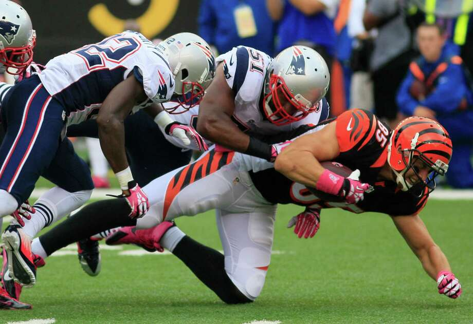 Cincinnati Bengals tight end Tyler Eifert (85) is tackled by New England Patriots outside linebacker Jerod Mayo (51) and free safety Devin McCourty (32) after a short gain in the first half of an NFL football game, Sunday, Oct. 6, 2013, in Cincinnati. (AP Photo/Tom Uhlman) ORG XMIT: PBS101 Photo: Tom Uhlman / FR31154 AP