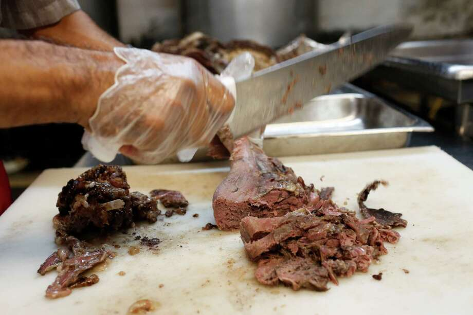 Manuel Martinez carves barbacoa from a cow's head at the shop on Patton where his boss, Jose Luis Lopez, has been cooking for 36 years. Photo: Eric Kayne / ©Eric Kayne 2013