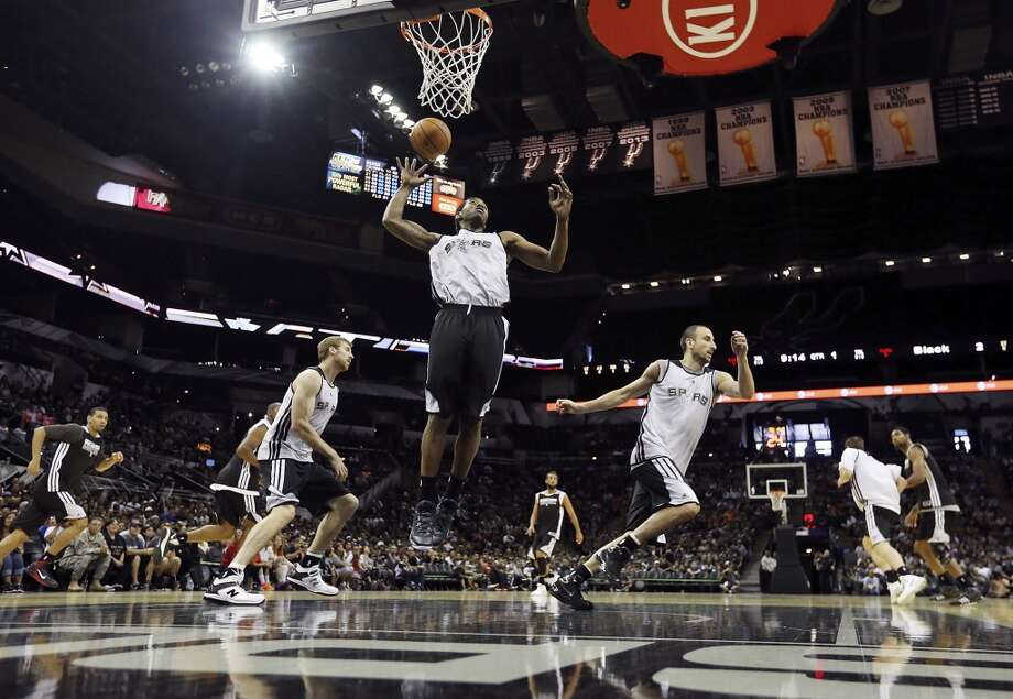Spurs' Kawhi Leonard (center) goes up for a rebound between teammates Matt Bonner (left) and Manu Ginobili  during an open scrimmage held Sunday Oct. 6 2013 at the AT&T Center. Photo: San Antonio Express-News