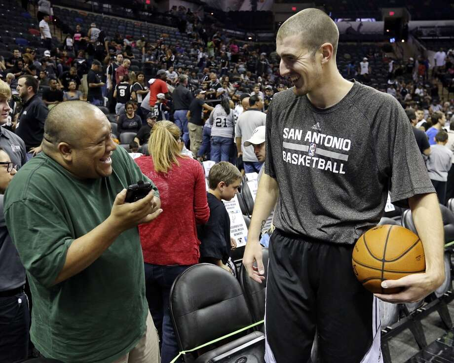 Jose Laurel (left) jokes with Spurs' Nando De Colo before an open scrimmage held Sunday Oct. 6 2013 at the AT&T Center. Photo: San Antonio Express-News