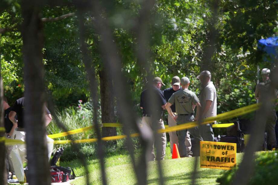 FBI agents conduct a search a upscale home on the 2000 block of Albans near Rice Village in the Southampton neighborhood Friday, Oct. 4, 2013, in Houston. Another site was being searched simultaneously at 411 Fall River Road in the Memorial area. Federal officials said they could not release other information because documents in the case have been sealed. Agents entering the home on Albans are wearing protective clothing, including purple gloves, white long-sleeve suits, and high, yellow boots. Two agents were also being suited up with masks rigged with a breathing apparatus. Photo: Johnny Hanson, Houston Chronicle / Houston Chronicle