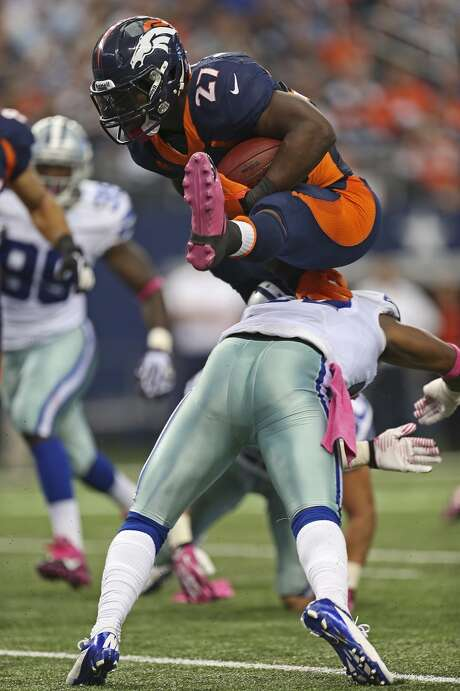 Denver Broncos' running back Knowshon Moreno jumps over Dallas Cowboys' J.J. Wilcox near the goal line in the first half at the AT&T Stadium in Arlington, Texas, Sunday, Oct. 6, 2013. Photo: San Antonio Express-News