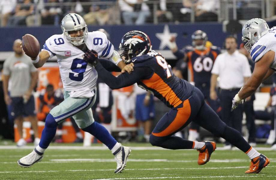 Dallas Cowboys' quarterback Tony Romo is sacked by Denver Broncos' Shaun Phillips in the first half at the AT&T Stadium in Arlington, Texas, Sunday, Oct. 6, 2013. Photo: San Antonio Express-News