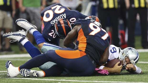Dallas Cowboys' quarterback Tony Romo hits the ground after he is tacked by Denver Broncos' Mike Adams, (20) and Malik Jackson, (97), on a quarterback keeper in the first half at the AT&T Stadium in Arlington, Texas, Sunday, Oct. 6, 2013. Photo: San Antonio Express-News