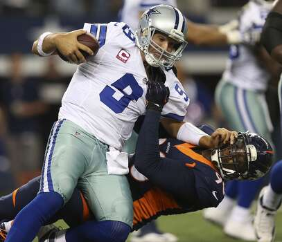 Dallas Cowboys' quarterback Tony Romo is sacked by Denver Broncos' Shaun Phillips late in the fourth quarter at the AT&T Stadium in Arlington, Texas, Sunday, Oct. 6, 2013. Romo threw an interception on the next play ending the Cowboy's chances. The Broncos won, 51-48. Photo: San Antonio Express-News