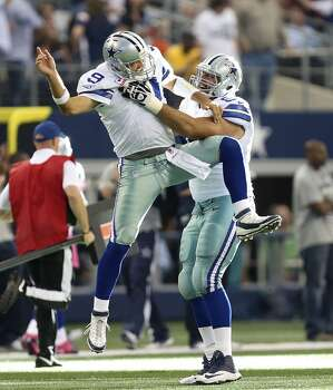 Dallas Cowboys' Tony Romo celebrates a touchdown pass with tackle Doug Free in the third quarter against the Denver Broncos at the AT&T Stadium in Arlington, Texas, Sunday, Oct. 6, 2013. The Broncos won, 51-48. Photo: San Antonio Express-News