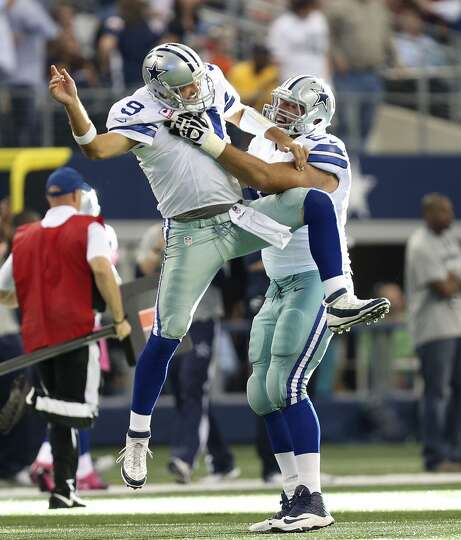 Dallas Cowboys' Tony Romo celebrates a touchdown pass with tackle Doug Free in the third quarter aga