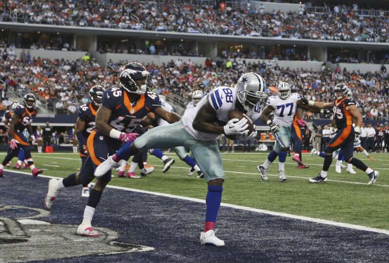 Dallas Cowboys' Dez Bryant pulls in a Tony Romo pass for a touchdown as Denver Broncos' D. Rodgers-C