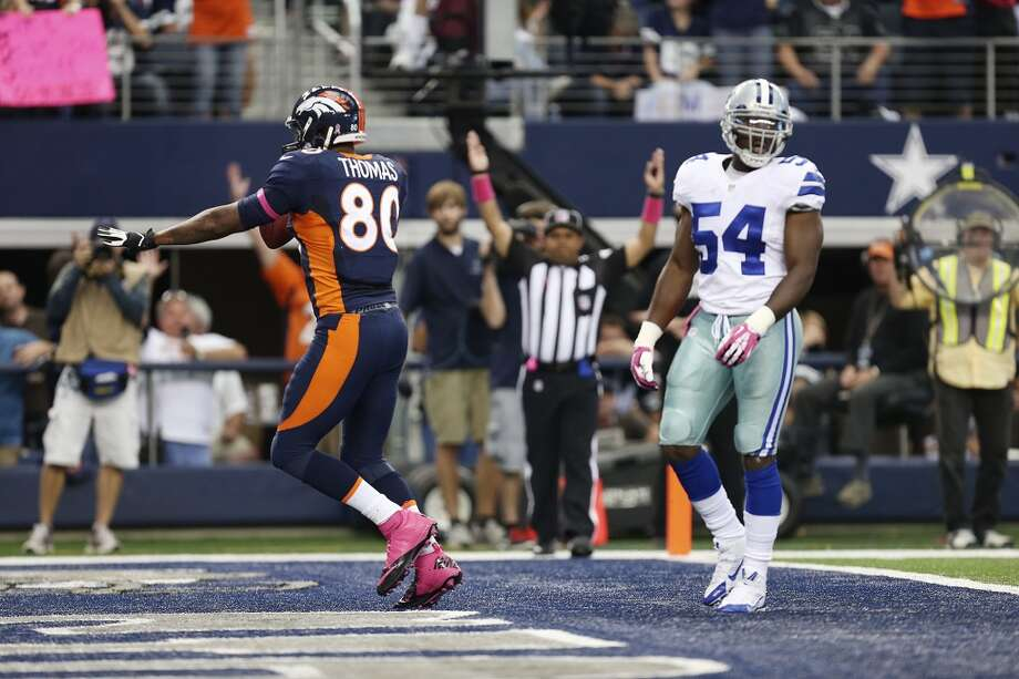 After scoring, Denver Broncos' Julius Thomas celebrates as Dallas Cowboys' Bruce Carter looks on in the first half at the AT&T Stadium in Arlington, Texas, Sunday, Oct. 6, 2013. The Broncos won, 51-48. Photo: San Antonio Express-News