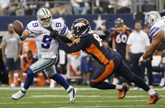 Cowboys quarterback Tony Romo, who was 25 of 36 for five touchdowns, a franchise-record 506 yards passing and one costly interception, is sacked by the Broncos' Shaun Phillips. Photo: Jerry Lara / San Antonio Express-News