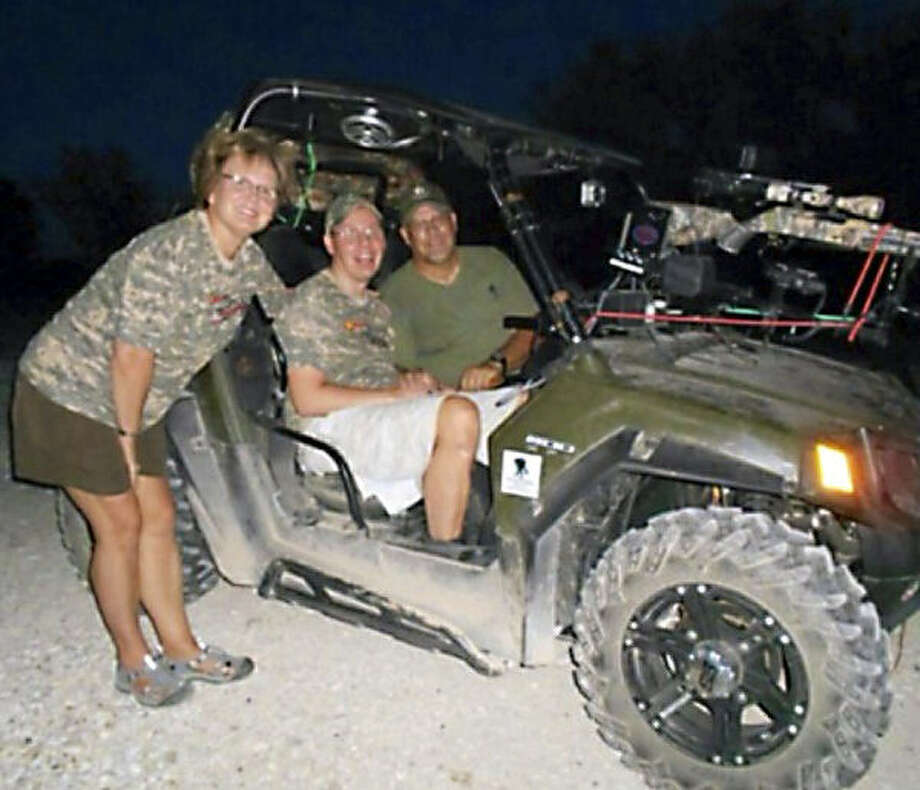 Eric Edmundson sits between his parents in his ATV, which was stolen in San Antonio. Photo: Courtesy Photo