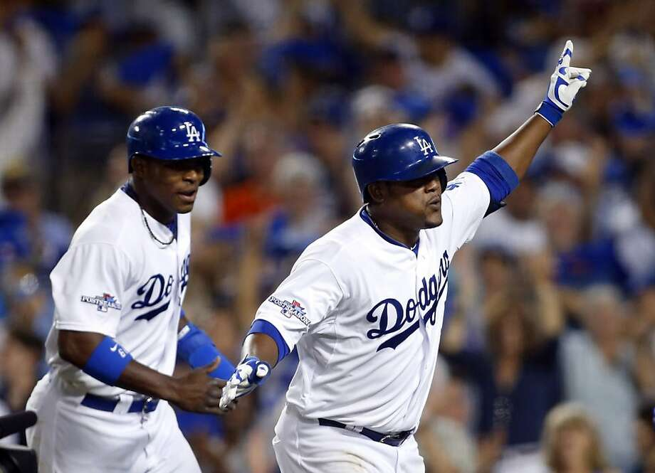 The Dodgers' Juan Uribe (right) celebrates after he hit a two-run home to score Yasiel Puig (left) in the fourth inning of Game 3 in Los Angeles. The homer gave the Dodgers a 10-4 lead. Photo: Danny Moloshok, Associated Press