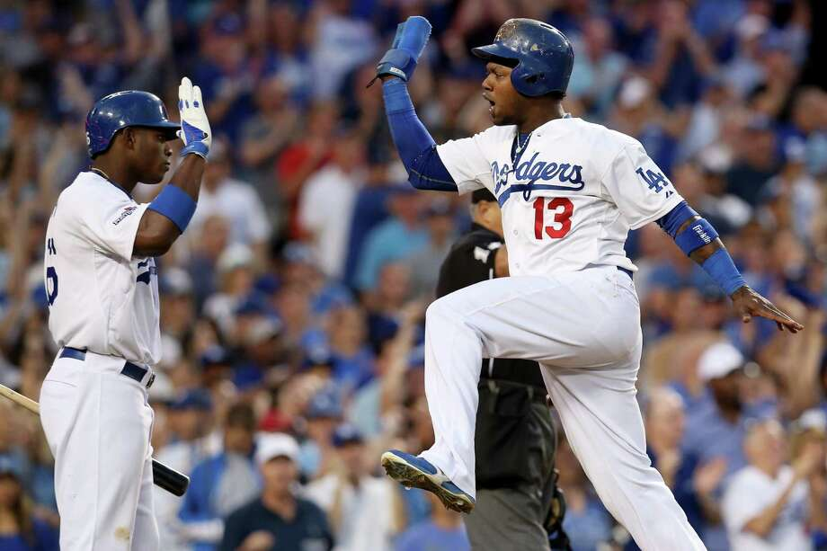 Hanley Ramirez, right, has a spring in his step as he scores in the third and celebrates with Yasiel Puig. Photo: Stephen Dunn, Staff / 2013 Getty Images