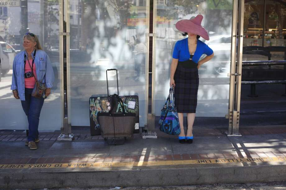 On her way to the Grace Alley Mural Project, street artist Eclair Bandersnatch waits for the bus in San Francisco, Calif. Photo: Mike Kepka, The Chronicle