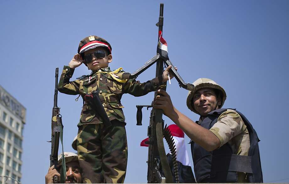 An Egyptian boy in an army costume salutes while posing next to army soldiers, from atop an armored vehicle guarding an entrance to Tahrir Square, in Cairo, Egypt, Sunday, Oct. 6, 2013. Egyptian jetfighters staged celebratory flights over Cairo on Sunday, ushering in a commemoration of the 40th anniversary of the nation's last war with Israel on a day when rival rallies by supporters and opponents of the ousted Islamist president carry the potential for violence. (AP Photo/Hassan Ammar) Photo: Hassan Ammar, Associated Press