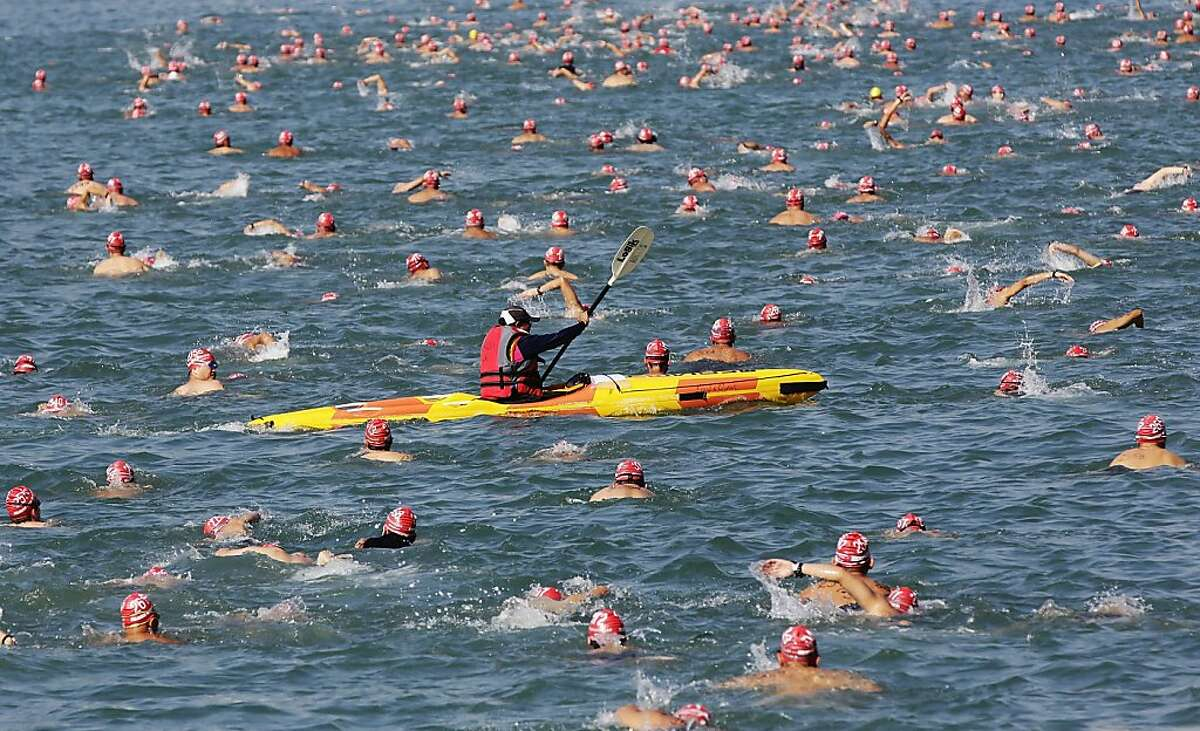 HONG KONG - OCTOBER 06: Swimmers make their way across Victoria Harbour during the New World Harbour Race on October 6, 2013 in Hong Kong. The 1.5 kilometer open water swimming race starts at Lei Yue Mun, Kowloon and finishes at Quarry Bay Park, Hong Kong Island, two thousand competitors are competing. (Photo by Jessica Hromas/Getty Images) *** BESTPIX ***