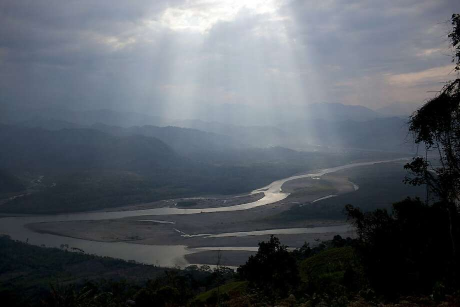In this Sept. 28, 2013 photo, sunlight filteres through the clouds, illuminating the Apurimac river in Pichari, Peru. The river cuts through a long valley that the United Nations says yields 56 percent of Peru's coca leaves. The government says it will soon begin destroying coca crops in the region, known as the VRAE - the Valley of the Apurimac and Ene rivers. (AP Photo/Rodrigo Abd) Photo: Rodrigo Abd, Associated Press