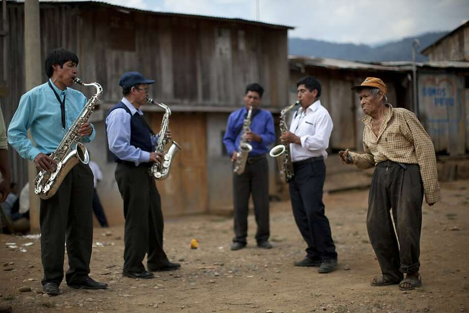 "In this Sept. 28, 2013 photo, a resident with castanets joins the ""La Roca Eterna"" evangelical orchestra as they perform during an annual church festival in Pichari, Peru. Pichari lies on the banks of the Apurimac river at the center of the world's No. 1 coca-growing valley. Coca is the lifeblood of the economy of Pichari, a mostly rural municipality of 40,000 people. (AP Photo/Rodrigo Abd) Photo: Rodrigo Abd, Associated Press"