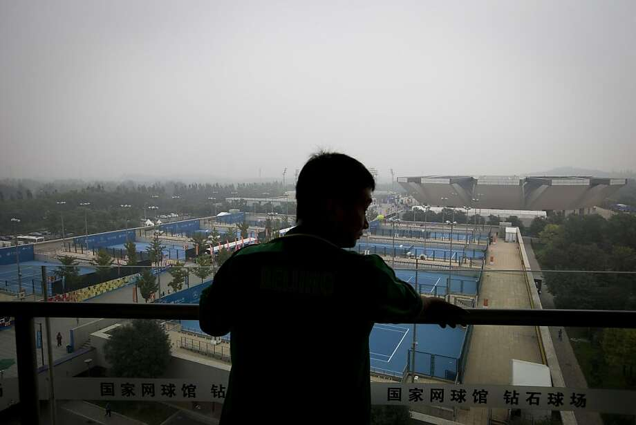 A man stands on the balcony of National Tennis Stadium looks at the tennis courts shrouded by haze in Beijing, China Sunday, Oct. 6, 2013. Fog and pollution descended on northern China on Sunday, leading to flight cancellations and road closures at a time when millions of Chinese were headed home as a weeklong national holiday neared its end. (AP Photo/Andy Wong) Photo: Andy Wong, Associated Press