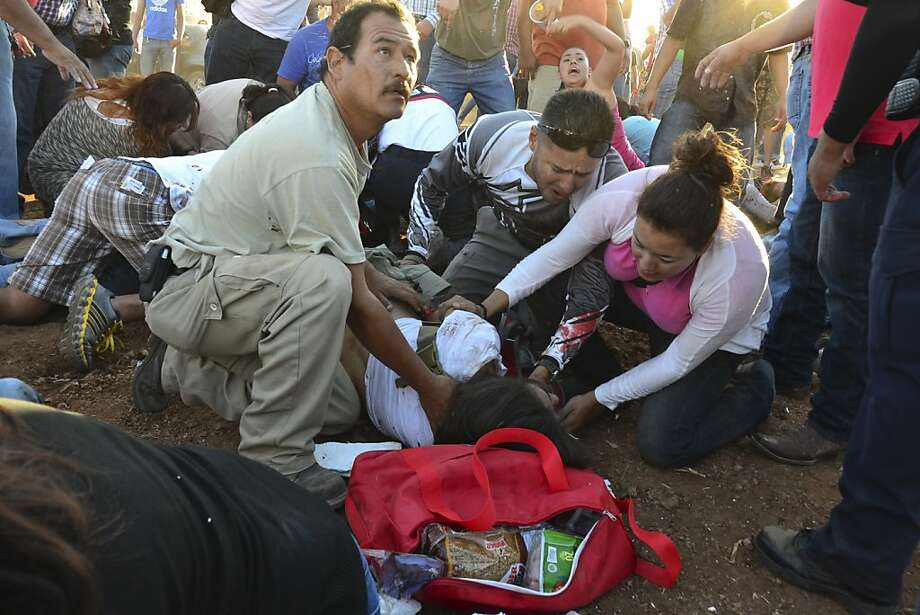Injured people are treated after an out of control monster truck plowed through a crowd of spectators at a Mexican air show in the city of Chihuahua, Mexico, Saturday Oct. 5, 2013. According to authorities, at least 8 people were killed and 80 were injured. (AP Photo/El Diario de Chihuahua) Photo: Associated Press