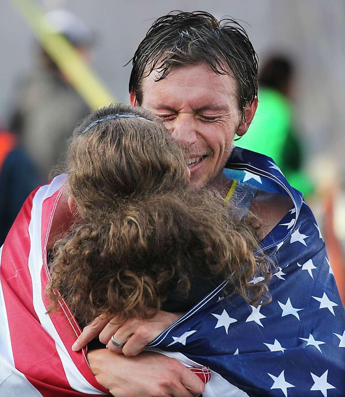 Nicholas Arciniaga, of Flagstaff, Ariz., hugs a supporter after winning the Medtronic Twin Cities Marathon in St. Paul, Minn., Sunday, Oct. 6, 2013. (AP Photo/Andy Clayton-King)