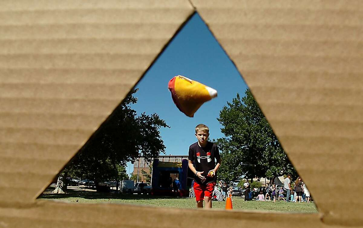 Wilson Player scores a bullseye in the bean bag toss Sunday, Oct. 6, 2013 during the Denny Price Family YMCA's Sundae in the Park at Government Springs Park in Enid, Oklahoma. (AP Photo/Enid News & Eagle, Billy Hefton)