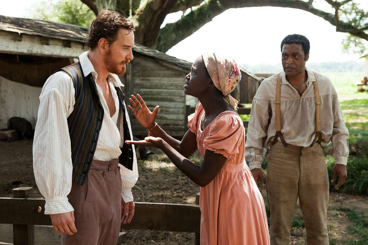 """This film publicity image released by Fox Searchlight shows, Michael Fassbender, from left, Lupita Nyong'o and Chiwetel Ejiofor in a scene from """"12 Years A Slave."""" The film, by director Steve McQueen, is being hailed a masterpiece and a certain Oscar heavyweight. (AP Photo/Fox Searchlight Films, Francois Duhamel)"""