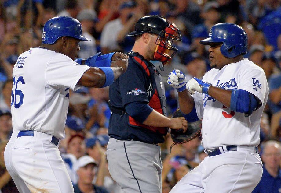 Los Angeles Dodgers' Juan Uribe, right, greets Dodgers' Yasiel Puig, left, at the plate next to Atlanta Braves catcher Brian McCann, center, after Uribe hit a two-run home run to score Puig in the fourth inning in Game 3 of the National League division baseball series Sunday, Oct. 6, 2013, in Los Angeles. (AP Photo/Mark J. Terrill) ORG XMIT: LAD148 Photo: Mark J. Terrill / AP